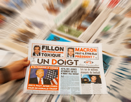 PARIS, FRANCE - JAN 21, 2017: Un Doigt - One Finger magazine above major international newspaper journalism featuring portrait of Donald Trump inauguration as the 45th President of the United States in Washington, D.C
