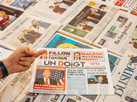 PARIS, FRANCE - JAN 21, 2017: Un Doigt - One Finger magazine above major international newspaper journalism and middle finger featuring portrait of Donald Trump inauguration as the 45th President of the United States in Washington, D.C