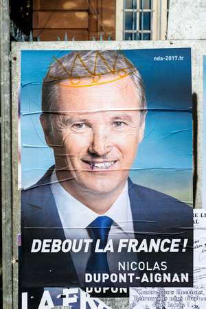 STRASBOURG, FRANCE - APR 26, 2017: Official campaign posters of Nicolas Dupont-Aignan, political party leader of Debout la France (DLF) vandalized on the first round of 2017 French presidential election