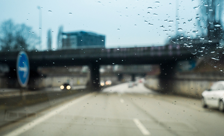 Personal perspective of driver inside car looking at the front view of the highway autobahn on a heavy rain
