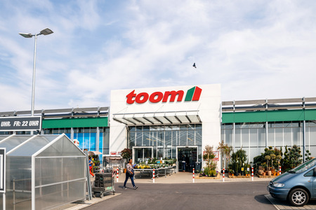 FRANKFURT, GERMANY - APR 1, 2017: Black ethnicity woman walking to the entrance of TOOM the German DIY-store chain offering home improvement and do-it-yourself goods - customers buying goods, selecting the best tools