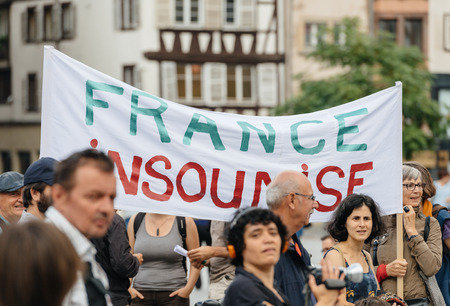 STRASBOURG, FRANCE - JUL 12, 2017: France Insoumise placard at protest against Macron government spending cuts and pro-business tax and labor reforms