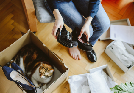 Woman unboxing unpacking several pairs of new shoes bought via online store demonstration showing them and curious cat pet inside the shipping box cardboard