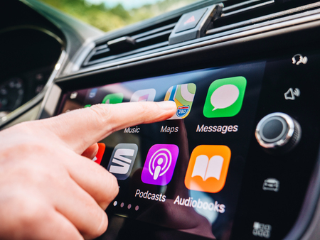 Photo pour PALMA DE MALLORCA, SPAIN - MAY 10, 2018: Woman pressing Apple Maps button on the Apple CarPlay main screen in modern car dashboard during driving on Spanish holiday highway - image libre de droit