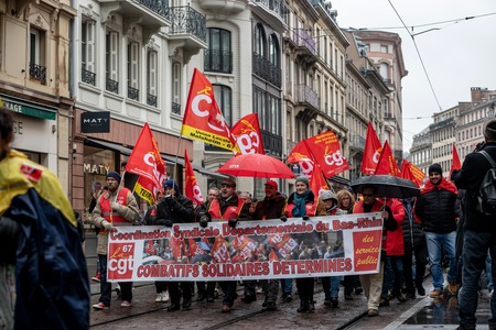 STRASBOURG, FRANCE - MAR 22, 2018: CGT General Confederation of Labour workers with placard at demonstration protest against Macron French government string of reforms - people with large banner combatif solidaires determines on closed street