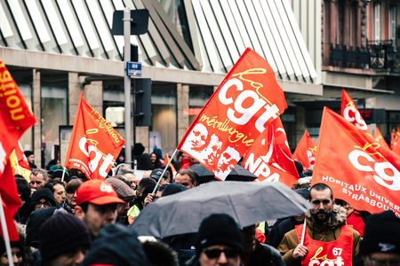 STRASBOURG, FRANCE - MAR 22, 2018: CGT General Confederation of Labour workers with placard at demonstration protest against Macron French government string of reforms - closed central street people with flags