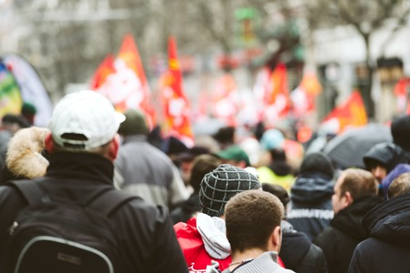 STRASBOURG, FRANCE - MAR 22, 2018: Rear view of crowd of protesters at CGT General Confederation of Labour workers with placard at demonstration protest against Macron French government string of reforms