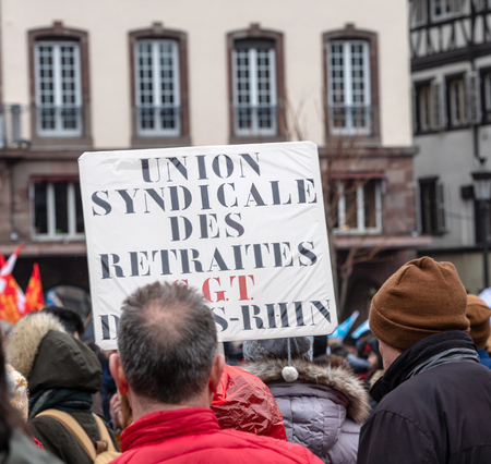 STRASBOURG, FRANCE - MAR 22, 2018: People gathering in Place Kleber square during CGT General Confederation of Labour demonstration protest against Macron French government string of reforms - retiree syndicates placard