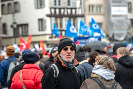 STRASBOURG, FRANCE - MAR 22, 2018: People gathering in Place Kleber square during CGT General Confederation of Labour demonstration protest against Macron French government string of reforms - man posing with crowd in background