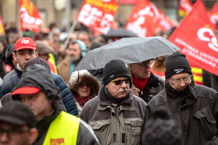 STRASBOURG, FRANCE - MAR 22, 2018: CGT General Confederation of Labour workers with placard at demonstration protest against Macron French government string of reforms - seniors men marching
