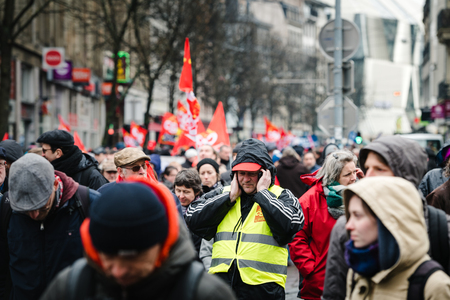 STRASBOURG, FRANCE - MAR 22, 2018: CGT General Confederation of Labour workers with placard at demonstration protest against Macron French government string of reforms - man covering ears due to high sound by sirens and yelings