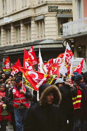 STRASBOURG, FRANCE - MAR 22, 2018: CGT General Confederation of Labour workers with placard at demonstration protest against Macron French government string of reforms - hundreds of people with red CGT flags