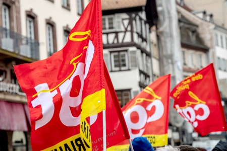 STRASBOURG, FRANCE - MAR 22, 2018: CGT General Confederation of Labour workers with placard at demonstration protest against Macron French government string of reforms - people waving CGT flags