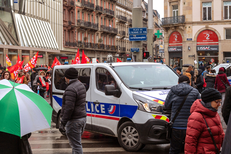 STRASBOURG, FRANCE - MAR 22, 2018: CGT General Confederation of Labour workers with placard at demonstration protest against Macron French government string of reforms - Renault police van surveillance of protestors in Place de lHomme de Fer