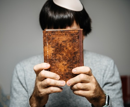 Photo for Jewish male wearing Kippah praying reading Bi-lingual Hebrew French mahzor prayer book from 1920 used on the High Holy Days of Rosh Hashanah and Yom Kippur holding book in front of the face. - Royalty Free Image