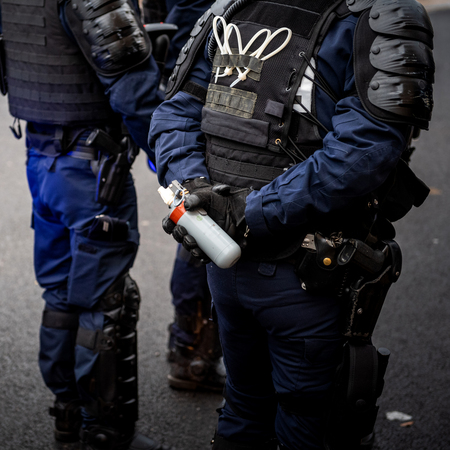 Foto de French Police officers securing the zone in front of the yellow vests movement protesters on Quai des Bateliers street woman officer with tear gas bottle ready to use it - square image, - Imagen libre de derechos