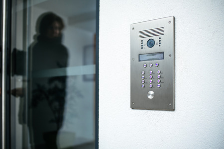 Photo pour Woman silhouette preparing to enter modern luxury home with focus on the door digital interphone - image libre de droit