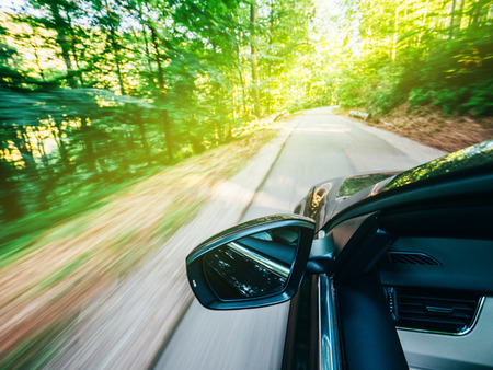 Photo pour Horizontal view of new modern car driving fast into forest with tall trees and empty mountain highway escaping running evading from all concept concept - image libre de droit