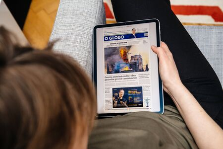 Foto de Paris, France - Apr 15, 2019: Woman reading O Globo on iPad Pro Apple News Plus digital newspaper featuring breaking news on cover French Notre-Dame Cathedral on fire causing damages - Imagen libre de derechos