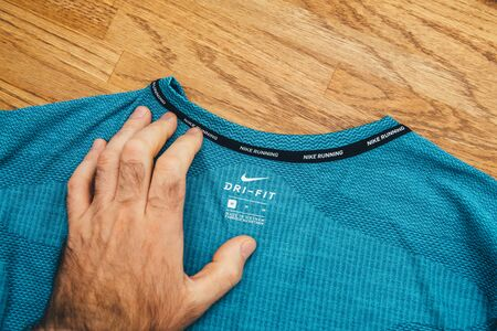 Paris, France - Jul 13, 2019: Man hand POV unboxing unpacking admiring latest sport clothes equipment for running manufactured byu Nike sportswear on wooden background tab le