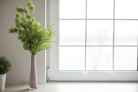 Photo pour Pink vase with green twigs stands in a bright cozy kitchen. Kitchen - image libre de droit