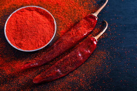 Foto per Red Chili pepper flakes and chili powder burst on black background - Immagine Royalty Free