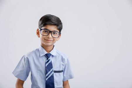 Photo pour Cute little Indian / Asian school boy wearing uniform and spectacles - image libre de droit