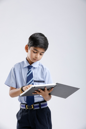Photo pour Cute little Indian/Asian school boy with spectacles reading book over white background - image libre de droit