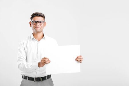 Photo for Young Indian business executive showing blank sign board over white background - Royalty Free Image