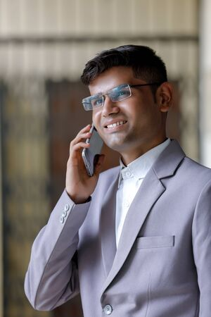 Young Indian Man Wearing Suit And Using Smartphone