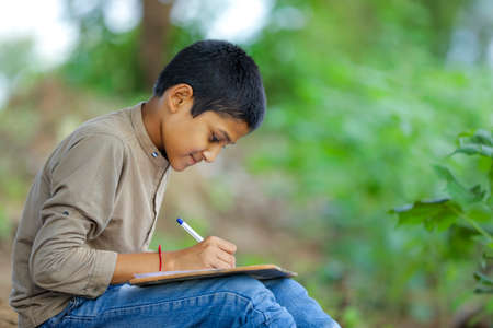 Photo pour Indian child writing on note book - image libre de droit