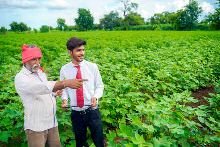 Photo pour Indian farmer with agronomist at Cotton field , showing some information on tab - image libre de droit