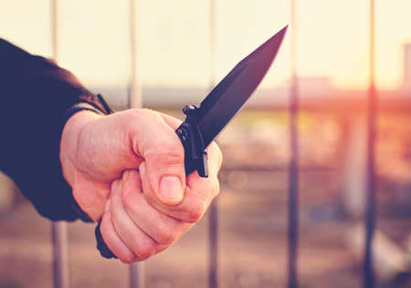 Hand with knife. Street violence concept.