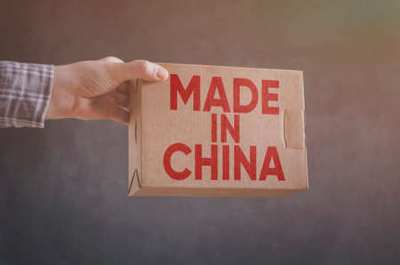 Photo pour Man`s hand with carton box with Made in China label imprint  - image libre de droit