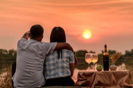 Foto de Happy life moments. Couple enjoying the sunset while having a glass of wine. - Imagen libre de derechos