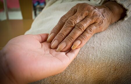 Photo pour hand of the sick old woman rests on the lap. Mental health care at home. - image libre de droit