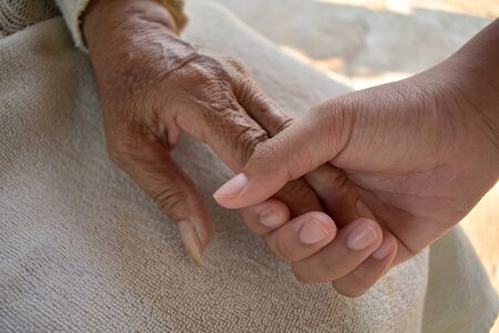 Photo pour Close up granddaughter takes care of the health sick grandmother at home by holding hands. Lifestyle support the love of the family. - image libre de droit