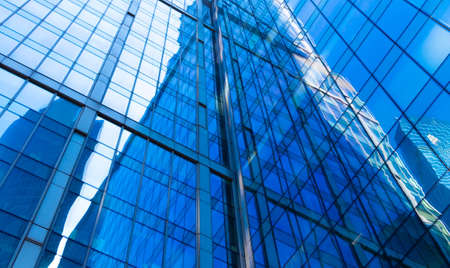 Foto de Reflection on glass facades of modern skyscraper in sunny day. Concept of business background with architecture details of financial district building - Imagen libre de derechos