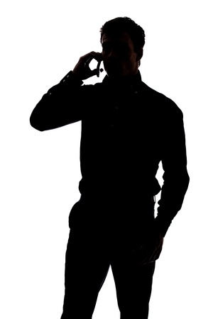 Photo pour Man talking on cell phone in silhouette isolated over white background - image libre de droit