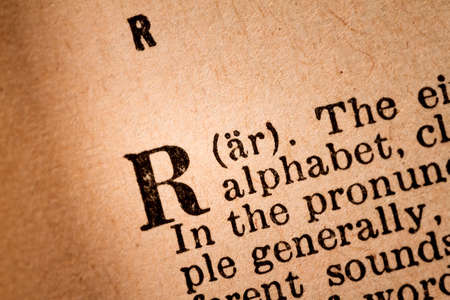 October 1st, 2015 - Montreal, Canada. Close-up of a R, the 18th Letter of the Latin Alphabet into a Old Pronunciation Dictionary