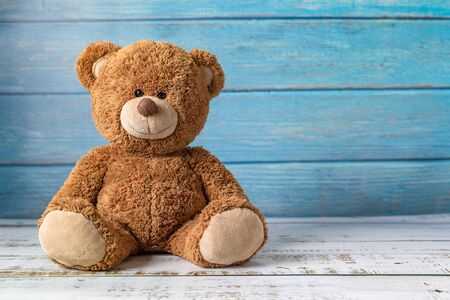 Foto de Cute teddy bear with copy space on blue color wood background. - Imagen libre de derechos