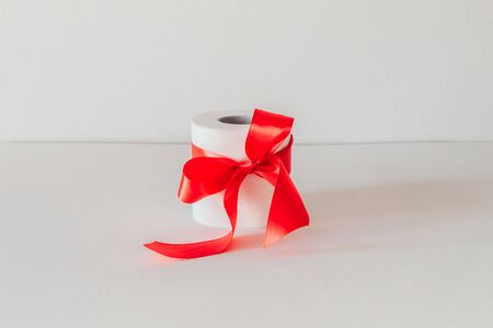 Photo for toilet paper with a red bow on a white background. - Royalty Free Image