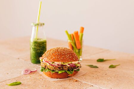Photo for Vegetarian burger with a bottle of green smoothie and carrot with celery in a glass. Stone beige table - Royalty Free Image