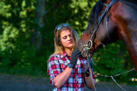 Beautiful girl with long hair on a walk with a horse. Summer evening.