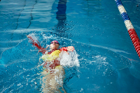 Photo pour Female athlete in a red-yellow swimsuit is swimming on his back. Splashes of water scatter in different directions. - image libre de droit