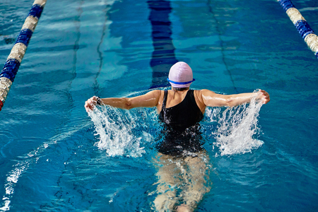 Photo pour Female athlete swims with a butterfly style. Splashes of water scatter in different directions. - image libre de droit