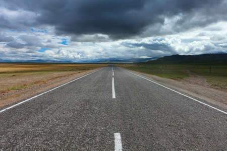 An empty desert road with dark and foreboding storm clouds on the horizon.