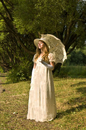 Young lady in white historical dress with white umbrella standing in park