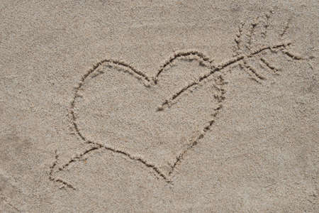 Photo pour heart and arrow drawing on sand sand background - image libre de droit