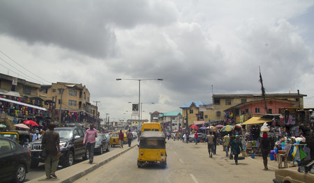 Photo pour LAGOS, NIGERIA - MAY 11, 2012: People in the street in the city view of Lagos, the largest city in Nigeria and the African continent. Lagos is one of the fastest growing cities in the world - image libre de droit